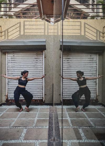 Full length of woman dancing reflection