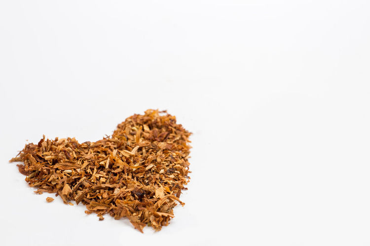 Isolate brown dry tobacco heart on white background. Love Medicine Objects RISK Shape Smoke Tobacco Addiction Bad Brown Cigarette  Dry Heap Heart Illness Leaf Lung Macro Narcotic Nicotine Object Pile Product Unhealthy Lifestyle White Background