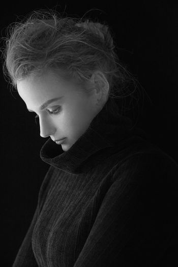 Thoughtful young woman standing against black background