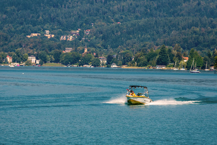 WORTHERSEE, AUSTRIA - AUGUST 08, 2018: View from the boat to the lake and coastline. Local residents and tourists swim, driven by motorboats and use other forms of water recreation. Nature Day Outdoors Austria Carinthia Carinthian Lakes Tourist Tourists Lake Wörthersee Recreation  Leisure Landscape Water Sea Boats Motorboat Speedboats Summer People Holidays Fun Travel Beach Resort Lifestyle Sunny Rest Joy Waves Europe Alps Alpine Alpine Lake Nautical Vessel Transportation Mode Of Transportation Motion Waterfront Tree on the move Beauty In Nature Sky Scenics - Nature Plant Sailing Land Passenger Craft
