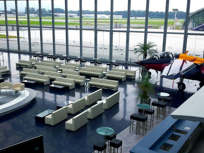 stylish white seats in a huge hall with Windows down till floor and plane at right side. Business Finance And Industry No People Outdoors Day Ladyphotographerofthemonth Hangar7 Salzburg Modern Modern Architecture Modern Interior Futuristic Architecture Futuristisch Seatings Large Windows Through A Window Salzburg Hangar7 Airport View Through The Window Bar Private Airplane Indoors  #urbanana: The Urban Playground