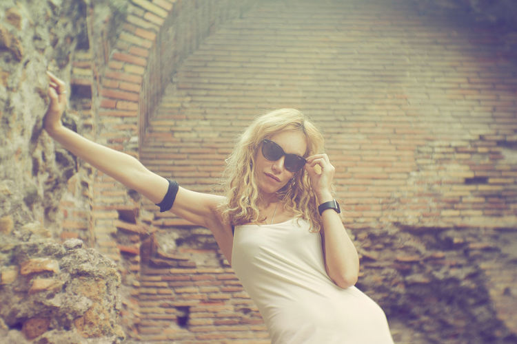 Portrait Of Woman In Sunglasses Standing Against Brick Wall