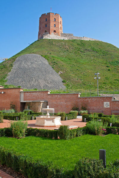 Gediminas' Tower or Castle, the remaining part of the Upper Castle in Vilnius, Lithuania with lithuanian flag waving on a green hill and blue sky photographed from a garden with fountain Baltic Castle Fountain Gediminas Gediminas Castle Gediminas Tower Holiday Lithuania Lithuanian Flag Travel Vilnius Wall Architecture Building Building Exterior Built Structure Day Garden Hill History Medieval Outdoors Reconstruction Sky Travel Destinations