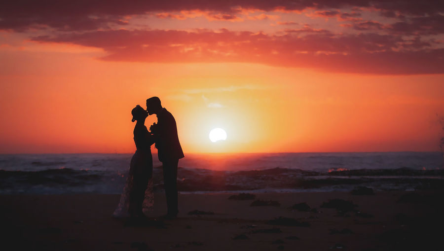 Silhouette Couple Kissing While Standing On Beach Against Sky During Sunset
