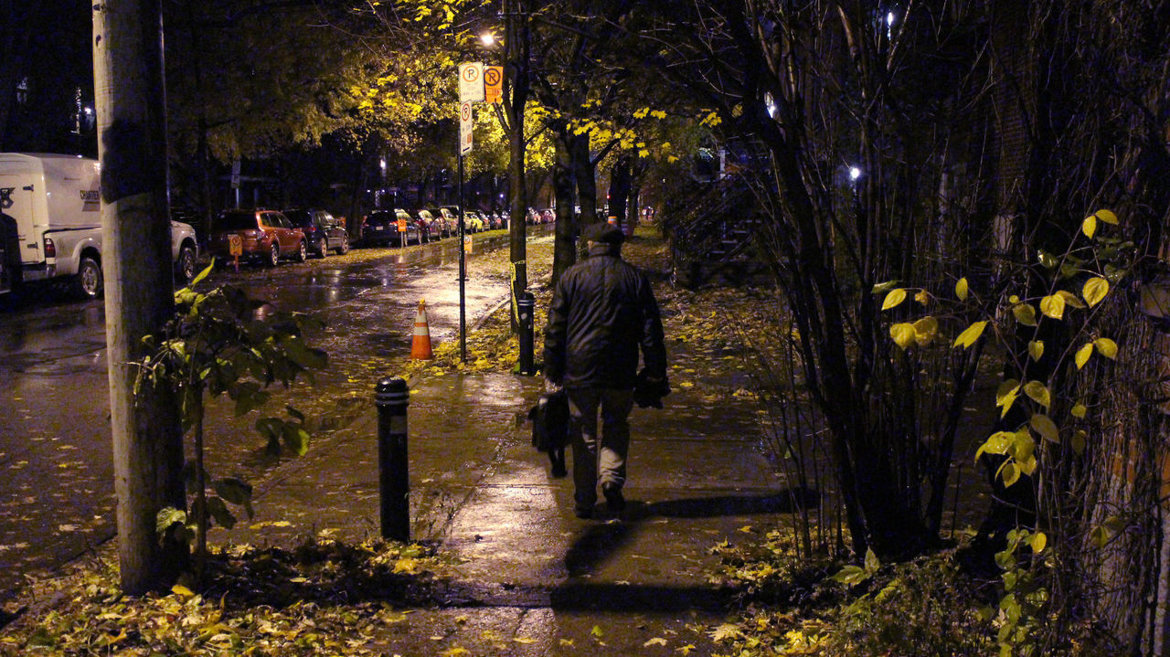 REAR VIEW OF PEOPLE WALKING ON FOOTPATH AT NIGHT