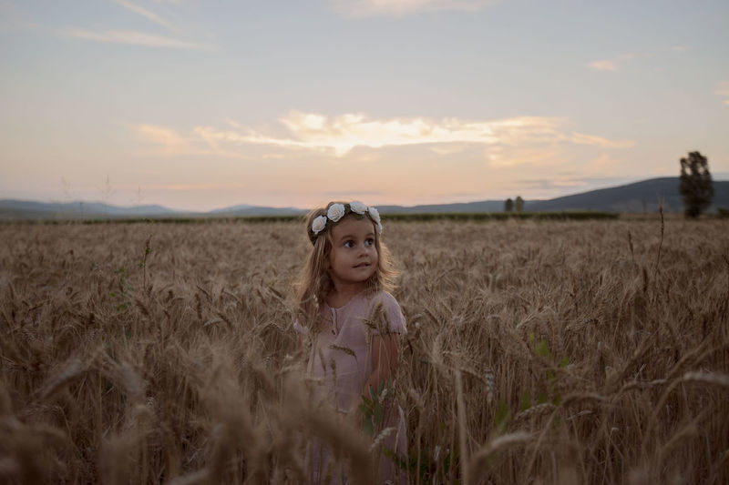 Girl Standing In Wheat Field Against Sky During Sunset