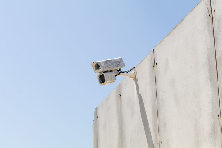 Low angle view of security camera on wall against clear sky