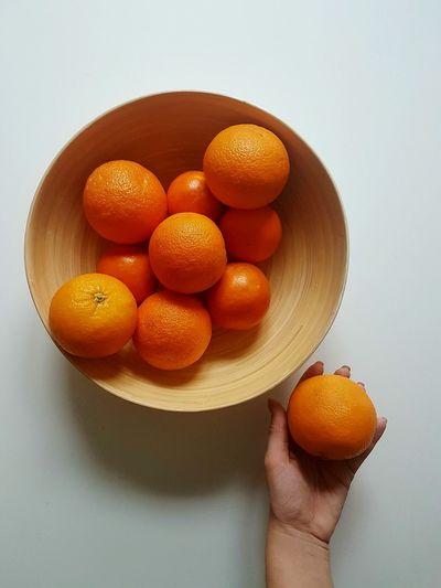 Close-up of hand holding orange fruit against white background