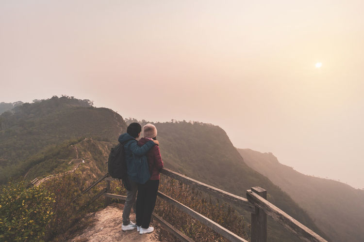 Rear view of couple standing on mountain during sunset