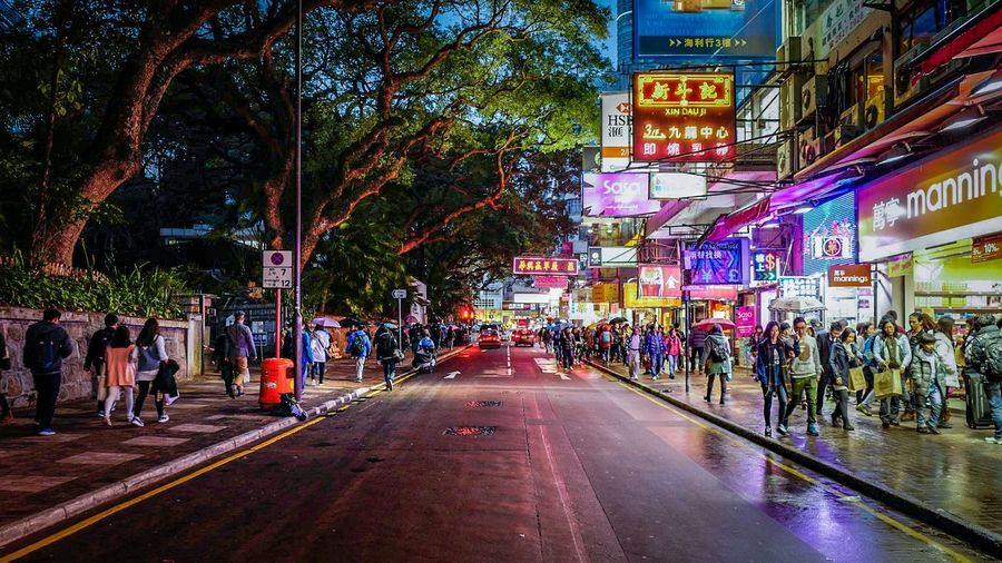 People walking on footpath in city at night
