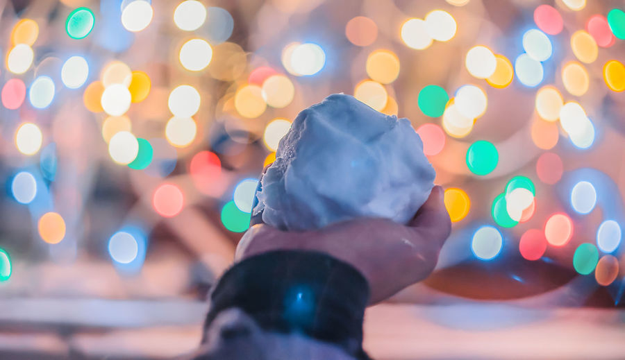 Close-up of hand holding snow at night