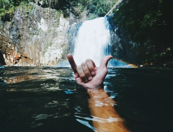 Person hand against waterfall