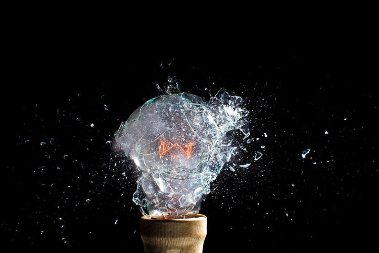 Close-up of light bulb breaking against black background