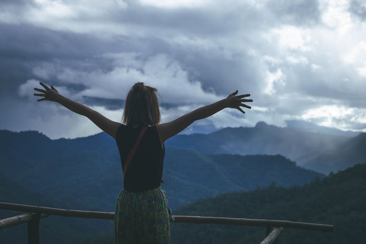 Rear view of woman looking at mountain range against sky