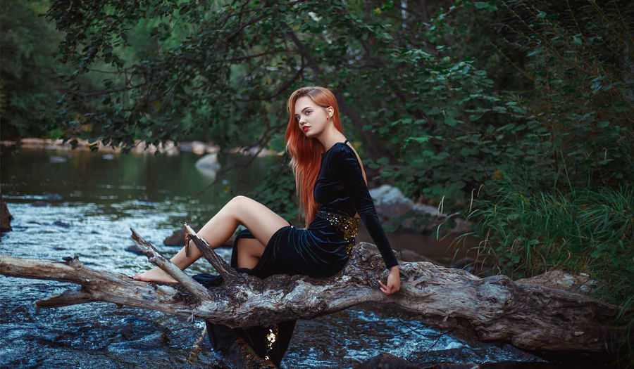 Young woman sitting at lakeshore in forest