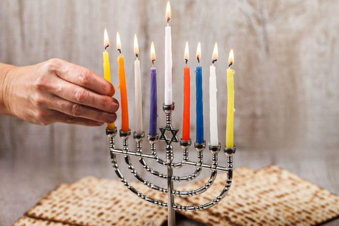 Menorah with candles for Hanukkah on a light wooden in the background. Burning Wood Adult Arts Culture And Entertainment Burning Candle Chanukah Close-up Finger Fire Fire - Natural Phenomenon Flame Hand Hanukkah Heat - Temperature Holding Human Body Part Human Hand Indoors  Matzo Matzoth Menorah Nature One Person Studio Shot Women Wooden