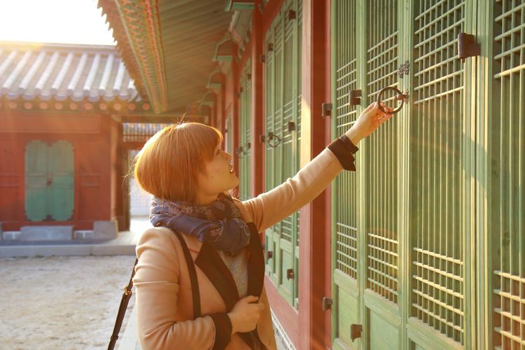 Woman holding door knocker while standing outdoors
