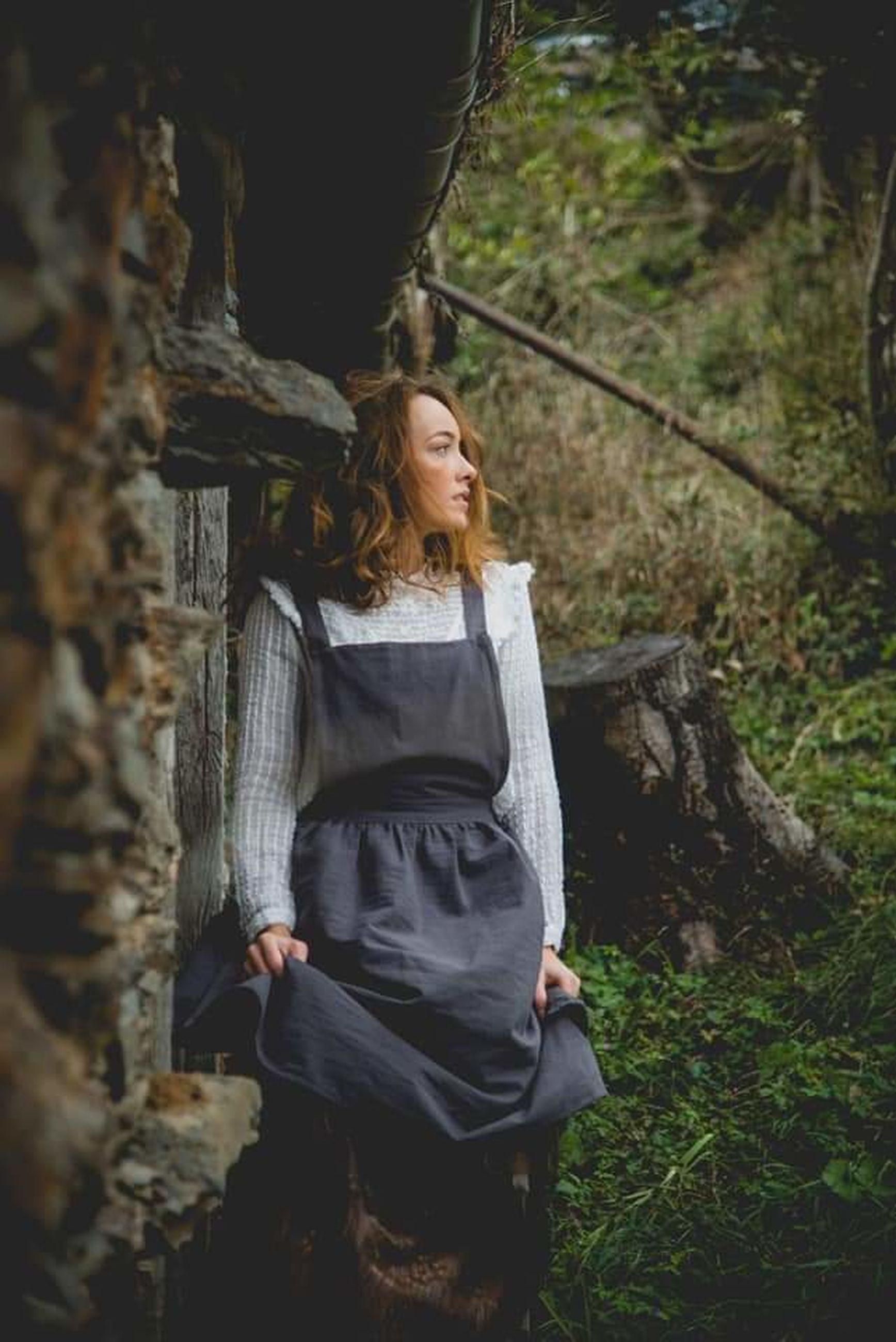 one person, adult, women, forest, tree, plant, nature, land, young adult, female, standing, woodland, lifestyles, three quarter length, leisure activity, outdoors, clothing, looking, person, dress, adventure, hairstyle, contemplation, spring, serious, portrait, beauty in nature, tranquility, front view, photo shoot, fashion, tree trunk, solitude