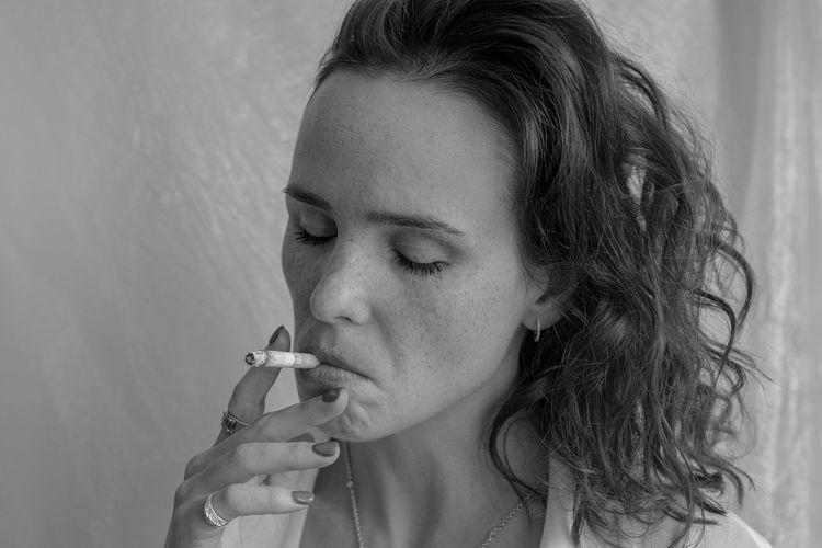 Close-up portrait of woman smoking cigarette