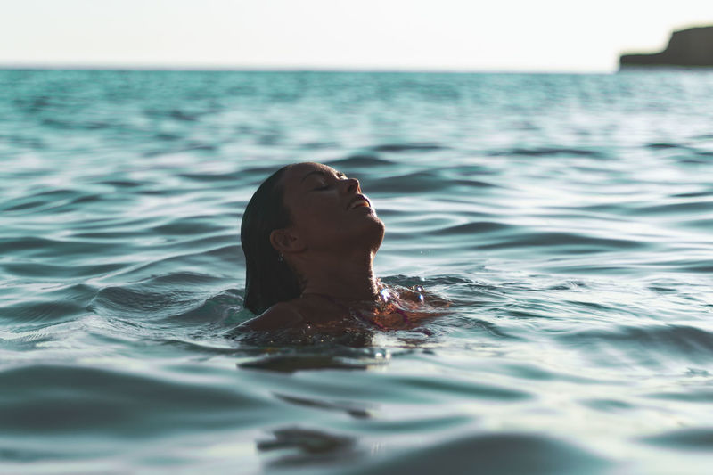 Close-up of woman on water surface of sea