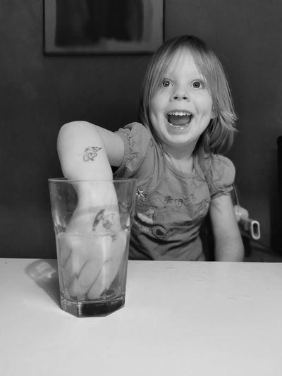 Portrait of a smiling girl sitting on table