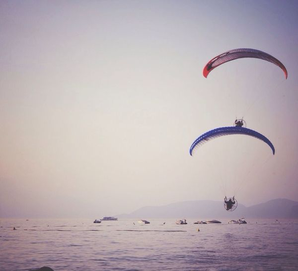 Low angle view of paragliders over sea against clear sky