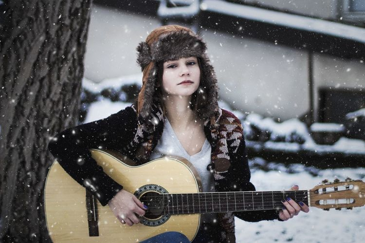 Portrait of woman playing guitar during snowfall