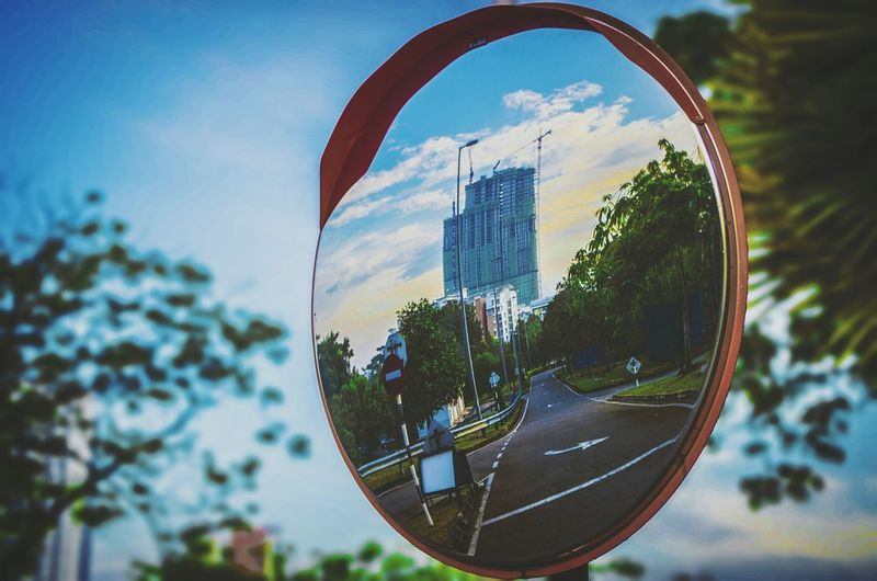 Street and buildings reflecting on road mirror in city