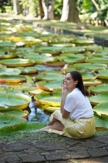 Thoughtful woman sitting by pond covered with lily pads