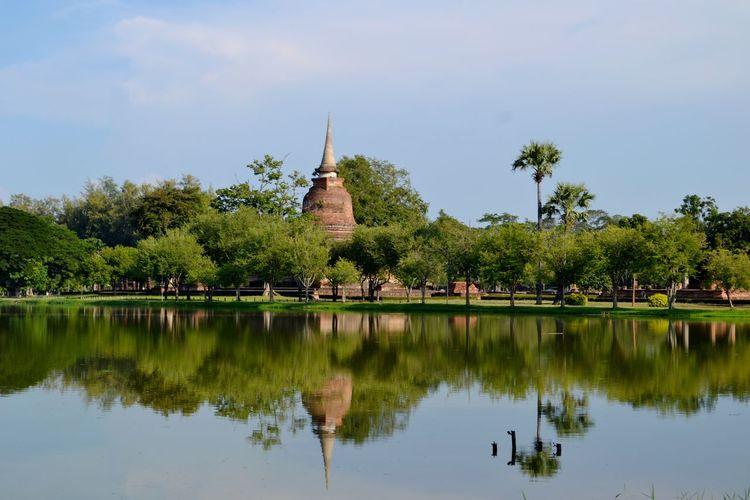 Reflection of stupa on calm lake at sukhothai historical park
