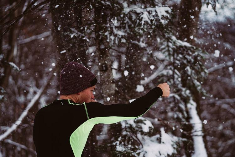 Man punching snowy tree