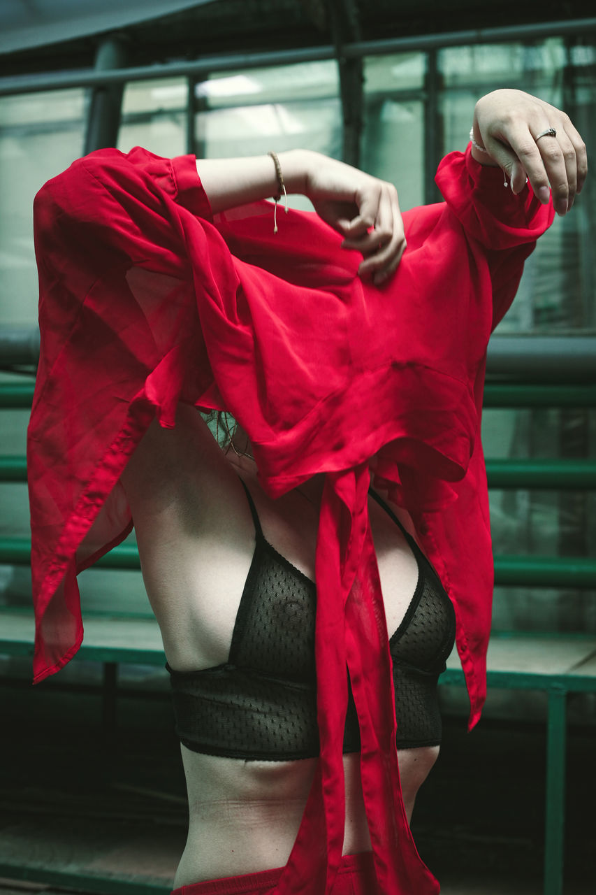MIDSECTION OF WOMAN HOLDING RED WHILE STANDING IN SHOP