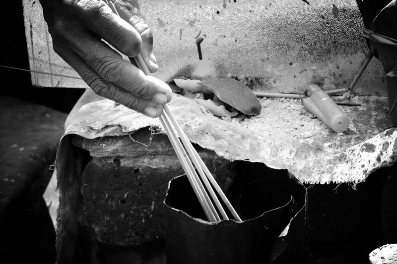 Cropped Hand Of Person Burning Incense Sticks At Temple