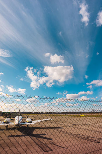 Privat airport. Heavy clouds in the blue sky. Airplane Privat Jet Propeller Airplane Airport Privat Airport Blue Sky Cloud - Sky Fence Countryside Airport Runway Passenger Boarding Bridge Airport Departure Area Airport Check-in Counter Barbed Wire Moving Walkway  Transportation Building - Type Of Building