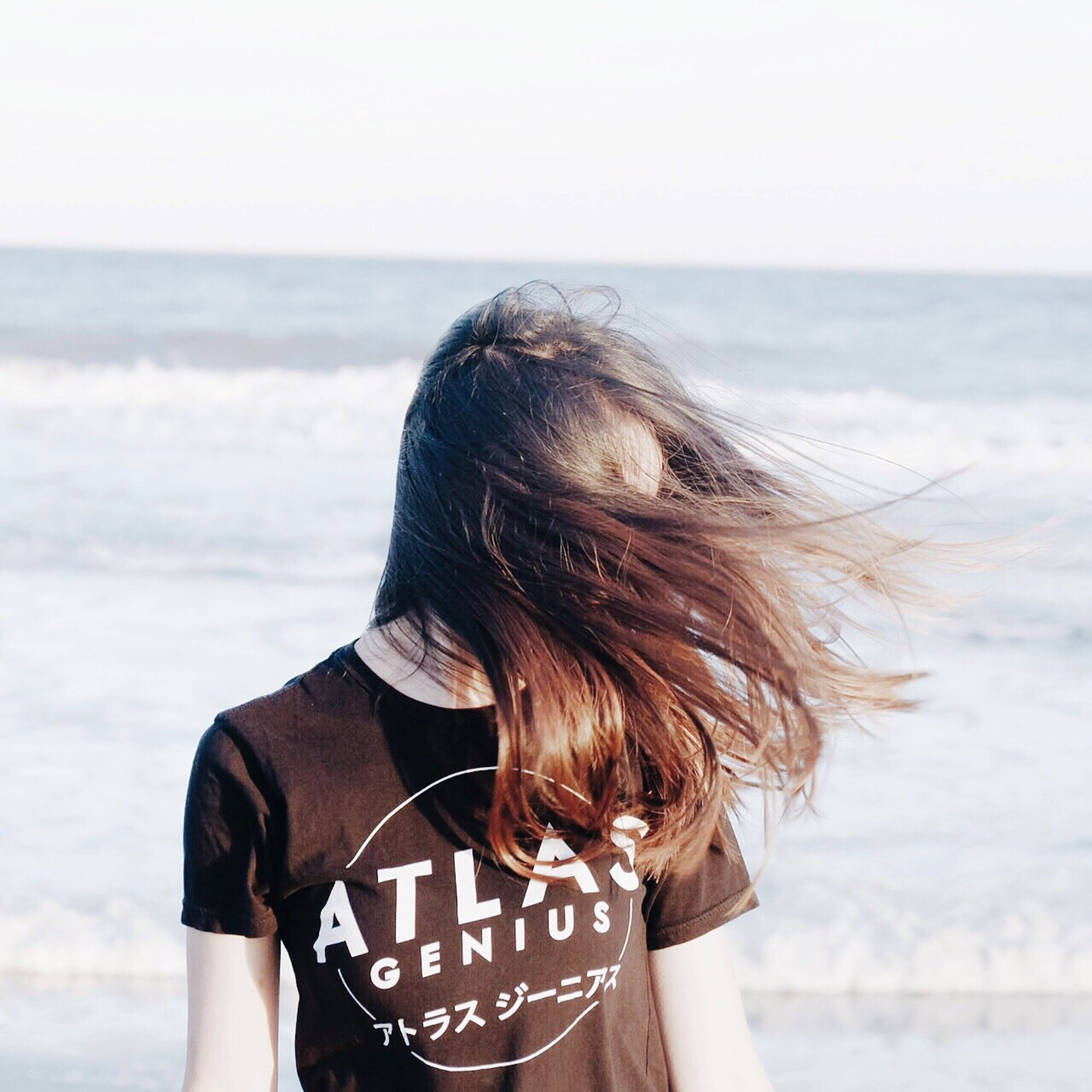 sea, horizon over water, rear view, lifestyles, focus on foreground, leisure activity, water, beach, person, standing, clear sky, sky, waist up, holding, long hair, nature, side view, beauty in nature