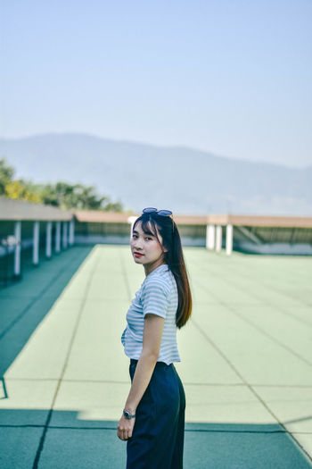 Portrait of young woman standing on floor at building terrace against sky
