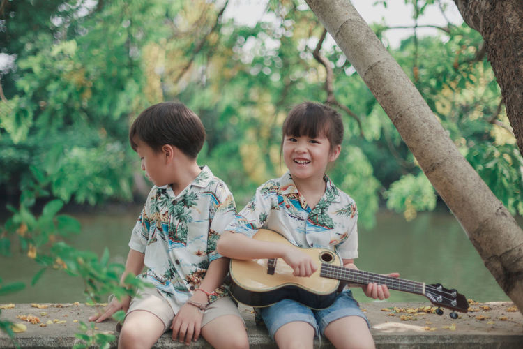 Portrait of girl playing guitar while sitting by brother on tree trunk