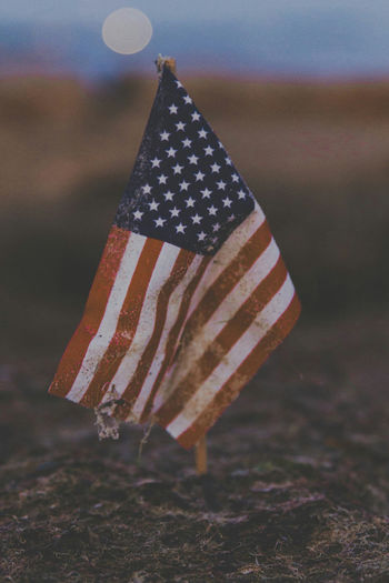 Close-up of weathered miniature american flag on field during sunset