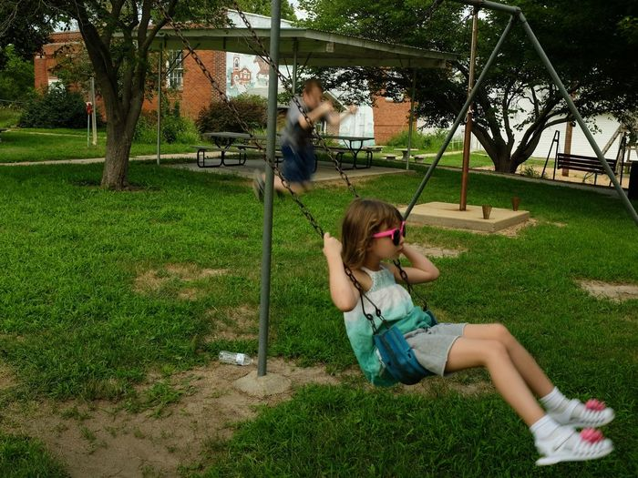 Full Length Of Girl Sitting On Swing At Park