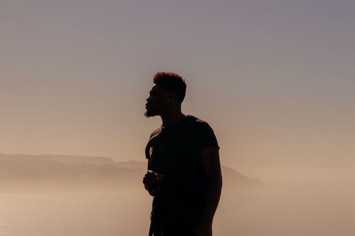 Man looking away while standing against sky during sunset