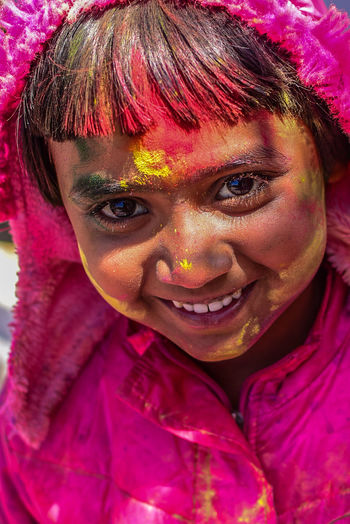 Close-Up Portrait Of Smiling Girl During Holi