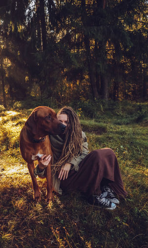Young smiling woman with dreadlocks in autumn fall forest in the morning sunshine playing with a dog ridgeback Mammal Land Domestic Pets One Animal Domestic Animals Canine Dog Plant Tree Real People Nature Vertebrate Field Forest Leisure Activity Adult People Pet Owner Outdoors Dreadlocks Ridgeback