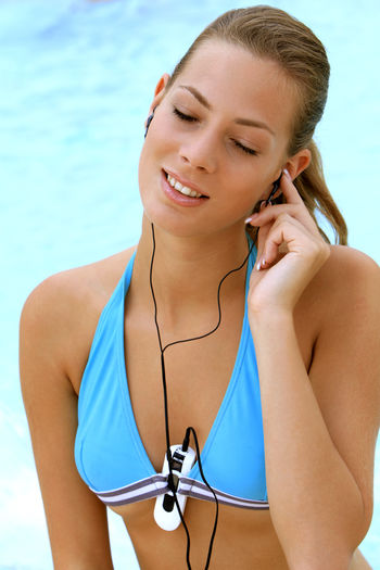 young blond woman listening to music with MP3 players at the pool Beautiful Happy Holiday Listening Music Music Summer Holidays Woman Beautiful Woman Bikini Blond Girl Happyness Leisure Leisure Activity Lifestyles Mp3 Player One Person Outdoors Pretty Relaxation Swimming Pool Vacation Water Wellbeing Young Adult