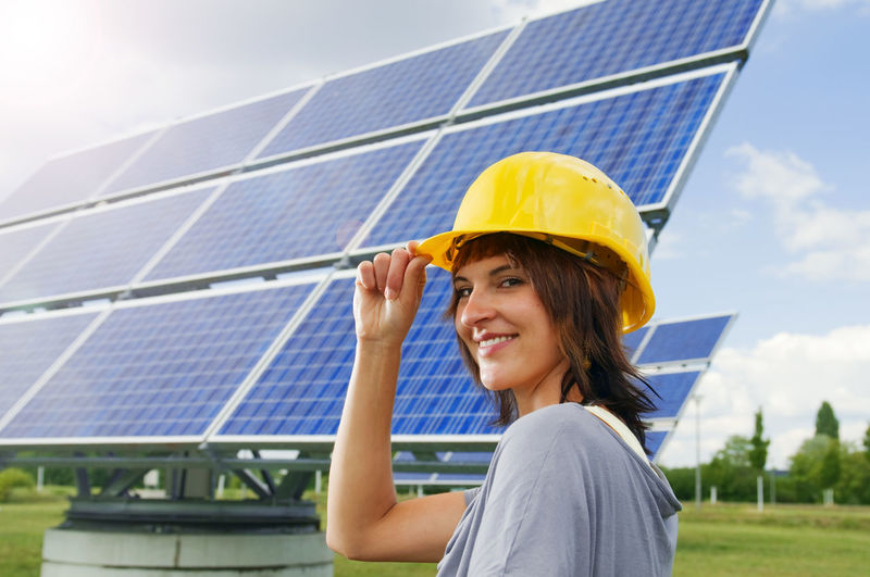 Side Head And Shoulders Portrait Of A Young Woman With Right Hand At Yellow Construction Site Helmet In Front Of A Photovoltaic Panel Satisfied Smiling At The Camera. Adult Alternative Energy Day Electricity  Environment Environmental Conservation Environmental Issues Fuel And Power Generation Hardhat  Helmet Lens Flare Nature One Person Outdoors Portrait Power Supply Renewable Energy Sky Smiling Solar Energy Solar Panel Sun Sustainable Lifestyle Sustainable Resources Technology