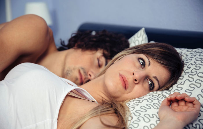 Thoughtful young woman looking away while lying near her asleep boyfriend. Couple relationship and problems concept. Angry At Home Bed Couple Horizontal Lifestyle Love Man Relationship Romantic Unhappy Woman Bedroom Caucasian Female Intimacy Male Problem Quarrel Real People Relax Resting Togetherness Two People Young Adult