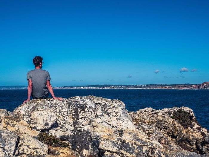 Rear view of man sitting on rock by sea against blue sky