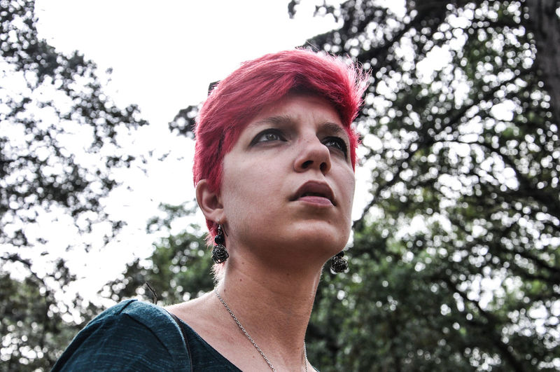 Low Angle View Of Thoughtful Young Woman With Dyed Hair Standing Against Sky In Forest