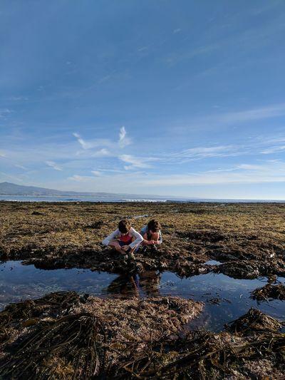 Friends crouching at beach against sky
