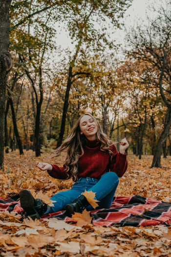 Smiling young woman sitting on autumn leaves against trees in forest