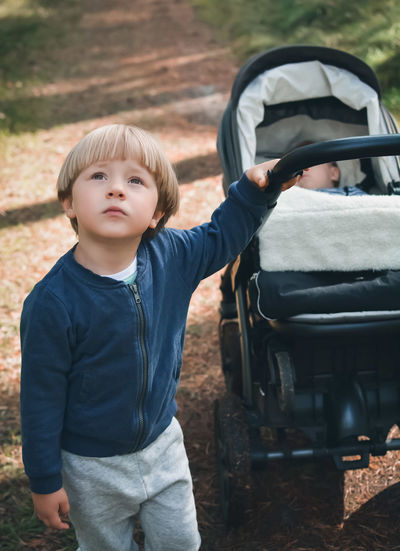 Boy holding stroller with baby boy at park